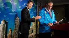 Mayor Gregor Robertson, left, welcomes openly gay Vancouver city councillor Tim Stevenson to the podium to speak after announcing Stevenson would represent the city at the 2014 Sochi Olympics, during a news conference in Vancouver, B.C., on Wednesday December 11, 2013. The City of Vancouver is responding to Russia's discrimination against gays and lesbians by proposing to send an openly gay councillor as its official representative for the 2014 Sochi Olympics. (DARRYL DYCK/THE CANADIAN PRESS)