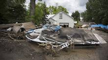 A displaced boat on someones front lawn damage caused by the massive flood in High River during a media tour of the city June 25, 2013. (John Lehmann/The Globe and Mail)