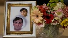 A photo of Robert Dziekanski, who was killed by a taser gun at the hands of RCMP at the Vancouver International Airport, sits on a table beside flowers at a press conference in Vancouver, B.C. October 25, 2007. (Jeff Vinnick for The Globe and Mail/Jeff Vinnick for The Globe and Mail)