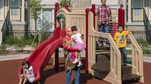 MISSISSAUGA, ONTARIO, CANADA: August 29, 2013 - (centre) Maimoona Mehmood, 34, Part-time Pizza Pizza employee, her husband (second from right) Syed Ali, 37, a trucking dispatcher, and their children (left) Zernaab, 5, (right) Wasi, 8, and (centre) Dania, 4, pose for a portrait at a playground behind their home at the Daniels Hazelton Place Phase Two development. ( Photo by Philip Cheung ) (Philip Cheung/Philip Cheung)