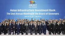 South Korean President Moon Jae-in, bottom center, poses with attendees for a group photo during a meeting of the Asian Infrastructure Investment Bank on Jeju Island, South Korea, Friday, June 16, 2017. (Bae Jae-man/AP)