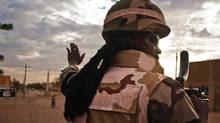 STOCK PHOTO: A Nigerian soldier rides atop an armoured vehicle during a patrol in the northern city of Gao, Mali February 9, 2013 (Francois Rihouay/Reuters)