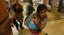 Women carrying children run for safety as armed police hunt gunmen who went on a shooting spree at Westgate shopping centre in Kenya on Sept. 21. The assault left at least 67 dead, with al-Shabab claiming responsibility. (GORAN TOMASEVIC/REUTERS)