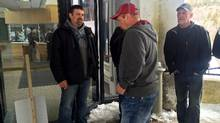 Fishermen from northeastern Newfoundland and southern Labrador are seen outside the DFO headquarters in St. John's on April 7, 2017 as police stand inside. (Sue Bailey/THE CANADIAN PRESS)
