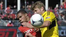 Toronto FC forward Ryan Johnson (L) and Columbus Crew forward Kirk Urso battle for the ball during the first half of their MLS soccer game in Toronto March 31, 2012. (Mike Cassese/REUTERS)