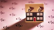 Miniature house on paper with percent symbols (Comstock/Getty Images/Comstock Images)