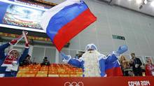 Empty seats are seen in the background as a skating fan dressed as Russia's Father Winter waves the national flag prior to the start of the men's 5,000-meter speedskating race at the Adler Arena Skating Center at the 2014 Winter Olympics, Saturday, Feb. 8, 2014, in Sochi, Russia. (Patrick Semansky/AP)