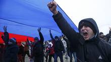 People march under a giant Russian flag during a pro-Russian rally in Simferopol, Crimea February 27, 2014. (David Mdzinarishvili/REUTERS)