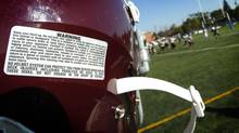 A warning sticker on a Humberside CI helmet warns against the injuries associated with football (file photo). (Peter Power/Peter Power/The Globe and Mail)