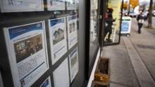 People walk past real estate listing posted in the window of a realty office in East Vancouver, British Columbia, Monday, November 4, 2013. (Rafal Gerszak For The Globe and Mail)