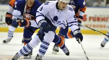 Toronto Maple Leafs' Colby Armstrong (9) drives the puck down ice ahead of New York Islanders' Radek Martinek (24), of the Czech Republic, during the third period of an NHL game, Tuesday, Feb. 8, 2011, in Uniondale, N.Y. (Kathy Kmonicek/AP)