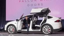 Elon Musk, chairman and chief executive officer of Tesla Motors Inc., exits the Model X sport utility vehicle (SUV) during an event in Fremont, Calif. on Tuesday, Sept. 29, 2015. Musk handed over the first six Model X SUVs to owners in California Tuesday night, as Tesla reached a milestone of having two all-electric vehicles in production at the same time. (David Paul Morris/Bloomberg)