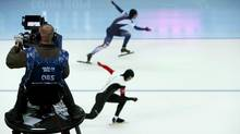 A televison camera follows the action as Gilmore Junio of Canada (BOTTOM) and Lee Kyou-hyuk of South Korea prepare to start in race two of the men's 500 meters speed skating event during the 2014 Sochi Winter Olympics, February 10, 2014. (MARKO DJURICA/REUTERS)