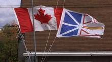 The Canadian and Newfoundland flags fly at half mast in Dover, Nfld. (CP/ANDREW VAUGHAN/CP/ANDREW VAUGHAN)
