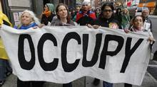 Occupy Wall Street demonstrators march while carrying a banner during what protest organizers called a 'Day of Action' in New York on Nov. 17, 2011. (JESSICA RINALDI/JESSICA RINALDI/REUTERS)