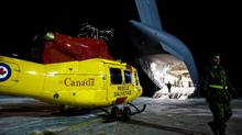 Military personnel prepare to load a Griffin helicopter on a CC-177 Globemaster on the tarmac at CFB Trenton for a Disaster Assistance Response Team, DART, humanitarian mission to earthquake ravaged Haiti. (Darren Calabrese/THE CANADIAN PRESS)