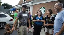 Open-carry supporters gather outside a Starbucks that closed early in response to their planned event in Newtown, Conn., Aug. 9, 2013. Starbucks, reversing a policy that had allowed customers to openly carry guns in states that allow it, said Sept. 18, 2013, that will now ask customers not bring firearms into its stores. The company said the policy was not a response to last year's shooting spree at Sandy Hook Elementary School in Newtown. (LISA WILTSE/NYT)