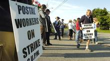Postal workesr walk a picket line at the Canada Post facility in Kitchener, Ont., on Friday, June 10, 2011. (Robert Wilson/The Canadian Press)