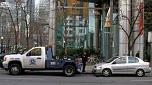 A car being towed on King St., in Toronto for parking during unauthorized time in rush hour. (Fernando Morales/The Globe and Mail.)