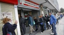 People stand in line to enter a government-run employment office in Madrid April 27, 2012. (ANDREA COMAS/REUTERS)