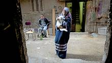 Mona, an Arabic teacher ,holds her white cat outside her shop in the Cairo suburb of ein Shams. (Heidi Levine/Sipa Press/Heidi Levine/Sipa Press)
