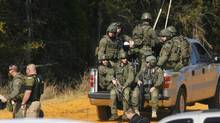 Law enforcement officials including the FBI are driven onto the scene of a shooting and hostage taking near Midland City, Alabama on Feb. 1, 2013. Residents in a rural Alabama town prayed on Friday and called for the release of a 5-year-old boy being held captive for a fourth day by a man accused of shooting a school bus driver and then taking the child hostage. (PHILIP SEARS/REUTERS)