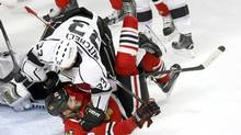 Los Angeles Kings defenseman Willie Mitchell (33) falls over Chicago Blackhawks left wing Bryan Bickell during the third period of Game 1 of the Western Conference finals on Sunday, May 18, 2014. (Charles Rex Arbogast/AP)