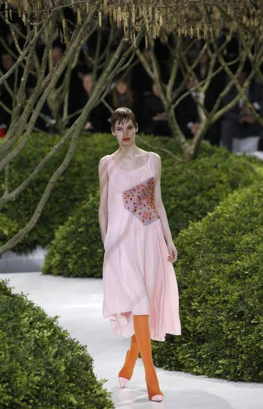 "Of his second haute couture collection for Christian Dior, Raf Simons said in the program notes, ""I wanted it to literally be about the season; to be about the very idea of spring."" As snow fell outside the tent, models emerged from below the runway into a sumptuous secret garden scene. (Christophe Ena/AP)"