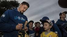 In this photo made on Thursday Jan, 5 2017, Ryan Lavarnway, an American professional baseball player, signs autographs to Israeli fans before the practice at the Baptist Village sport complex near Petah Tikva, Israel. (Tsafrir Abayov/AP)