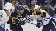 Buffalo Sabres forward William Carrier gets tied up with Toronto Maple Leafs Connor Carrick during the first period in Buffalo on Monday. (Jeffrey T. Barnes/The Associated Press)