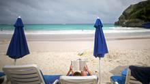 A vacationer relaxs on the beach of the The Crane hotel in St. Philip, Barbados, on April 10, 2010. (YANA PASKOVA)