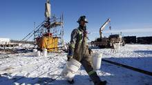 A worker walks past the wellhead at a hydraulic fracturing operation near Bowden, Alta., Tuesday, Feb. 14, 2012. (Jeff McIntosh/Globe and Mail)