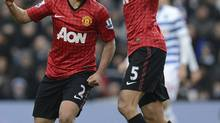 Manchester United's Rafael da Silva (L) celebrates scoring with Rio Ferdinand against Queens Park Rangers during their English Premier League soccer match in London February 23, 2013. (NIGEL RODDIS/REUTERS)