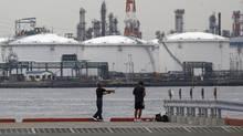Men fish near an oil refinery in Kawasaki, near Tokyo July 5, 2012. (Toru Hanai/REUTERS)