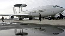 Hungarian soldiers stand next to a NATO AWACS (Airborne Warning and Control System) aircraft at the tarmac of the millitary airbase of Kecskemet, 90km east of Budapest January 25, 2007. (Laszlo Balogh/Reuters/Laszlo Balogh/Reuters)