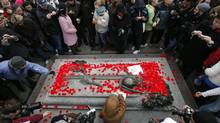 People lay poppies on the Tomb of the Unknown Soldier following Remembrance Day ceremonies at the National War Memorial in Ottawa November 11, 2011. (Blair Gable/Reuters)