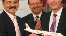Rusdi Kirana, left, chief executive of Indonesia's Lion Air, and Fabrice Bregier, chief executive of Airbus SAS, right, pose for the media with France's President Francois Hollande in Paris, March 18, 2013, after Lion Air placed its $24-billion Airbus order. (Michel Euler/AP)