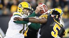 Edmonton Eskimos quarterback Mike Reilly (13) fakes a pass and holds the ball while under pressure from the Hamilton Tiger-Cats Adrian Tracy during the first half of CFL football action in Hamilton on Friday, October 28, 2016. (Peter Power/THE CANADIAN PRESS)