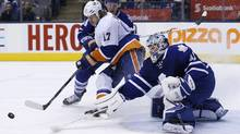 Toronto Maple Leafs goalie Jonathan Bernier, right, makes a save on New York Islanders Matt Martin as Toronto Maple Leafs Morgan Rielly, left, skates to the play during first period NHL hockey action in Toronto, Tuesday November 19, 2013. (The Canadian Press)