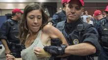 A demonstrator is taken away by a police officer after disrupting the National Energy Board public hearing into the Energy East pipeline project in Montreal on Monday. (Paul Chiasson/The Canadian Press)