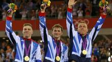 Britain's Philip Hindes stands with his gold medals during the victory ceremony after the track cycling men's team sprint finals at the Velodrome during the London 2012 Olympic Games August 2, 2012. (CATHAL MCNAUGHTON/REUTERS)