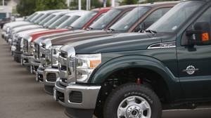 2011 Ford F-350 pickup trucks sit at a dealership