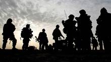 Canadian soldiers are silhouetted during a village search and security operation in the Dand area of Kandahar Province, southern Afghanistan, on Jan. 26, 2010. (Kirsty Wigglesworth/AP)