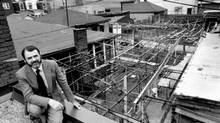 Michael Hough, seen in 1985, perches on a Toronto rooftop overlooking a jumble of sheds, fences, wires, laundry lines and vines, which he said he found 'absolutely stunning.' (Edward Regan/The Globe and Mail)