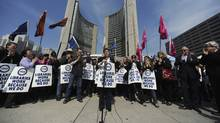 Maureen O'Reilly (centre behind microphone), president of CUPE Local 4948, addresses Toronto public library workers gathered outside City Hall on March 19, 2012. Toronto's 2,300 library employees walked off the job after 5 p.m. Sunday, shuttering 98 branches across the city. (Fred Lum/The Globe and Mail/Fred Lum/The Globe and Mail)