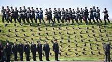 Soldiers walk past boots sitting on the lawn at the Canadian National Vimy Memorial during a commemoration ceremony to mark the 100th anniversary of the Battle of Vimy Ridge, in Vimy, France, on April 9, 2017. (Philippe Huguen/Reuters)