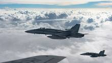 Royal Canadian Air Force CF-18 Hornets depart after refuelling with a KC-135 Stratotanker assigned to the 340th Expeditionary Air Refueling Squadron, Thursday, Oct. 30, 2014, over Iraq. The Canadian military reported 18 new air strikes against targets belonging to the Islamic State in Iraq and the Levant, but none in the latest round involve missions over Syria. (Staff Sgt. Perry Aston/THE CANADIAN PRESS)