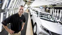 Brian Krinock, president of Toyota Motor Manufacturing Canada Inc., poses with new vehicles being built on the line at the Lexus plant in Cambridge, Ont., on Wednesday. (Peter Power for The Globe and Mail)