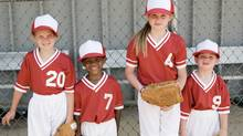 Children in baseball uniforms standing by fence with gloves Credit to Thinkstock (Creatas Images)