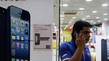 A man speaks on his mobile phone while standing next to posters advertising an Apple iPhone 5 and Blackberry Z10 in Ahmedabad Feb. 22, 2013. (AMIT DAVE/Reuters)